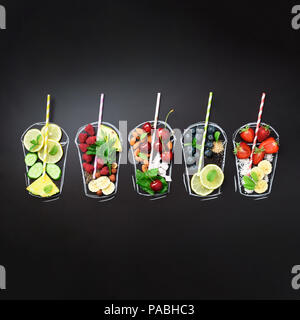 Painted glasses with fresh food ingredients for smoothies, drinks on black chalkboard. Square crop. Assortment of colorful juices, beverages. Top view - Stock Photo