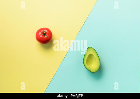 Green sliced avocado and red tomato on blue and yellow background. Top view. Pop art design, creative summer food concept. Minimal flat lay style - Stock Photo