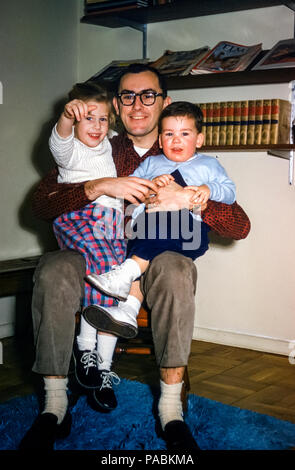 1950s family with father wearing glasses and two young children sitting on lap in sitting room with book shelves, New York state, USA. Digital conversion of historical photo taken in 1959 - Stock Photo