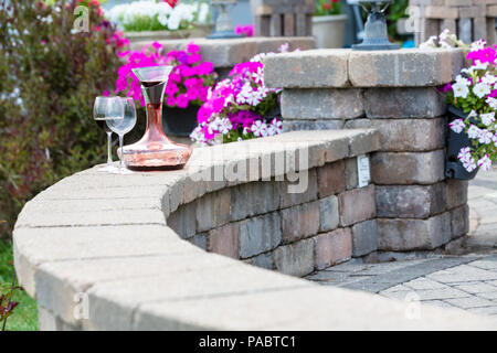 Decanter of red wine aerating on a curved brick patio wall with two wineglasses in front of colorful potted summer flowers with copy space - Stock Photo