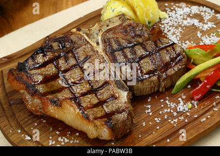 Roasted BBQ T-Bone Steak and herb butter on wooden cutting board - Stock Photo