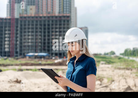 Female construction engineer. Architect with a tablet computer at a construction site. Young Woman looking, building site place on background. Construction concept - Stock Photo
