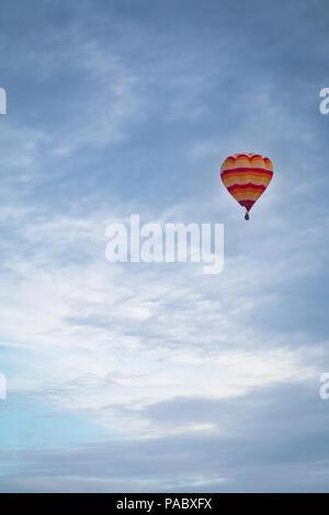 A single hot air balloon rises away over the Knavesmire in York during York Balloon Fiesta. - Stock Photo