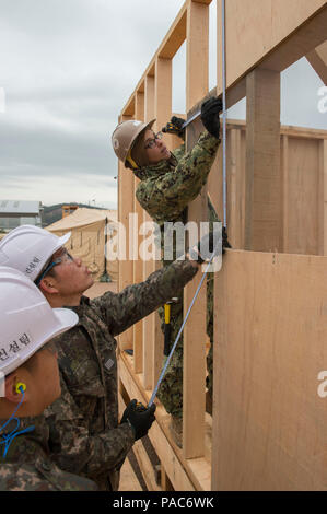 160309-N-HA376-023 BUSAN, Republic of Korea (March 9, 2016) - U.S. Navy Builder 3rd Class Marcell Cupello, assigned to Naval Mobile Construction Battalion (NMCB) 133, and Republic of Korea (ROK) Seabees measure a wall section on a Southwest Asia Hut during exercise Foal Eagle 2016. NMCB 133 and ROK Seabees are working hand-in-hand to construct various expeditionary facilities during the exercise. Foal Eagle is an annual, bilateral training exercise designed to enhance the readiness of U.S. and ROK forces, and their ability to work together during a crisis. (U.S. Navy photo by Chief Mass Commun - Stock Photo
