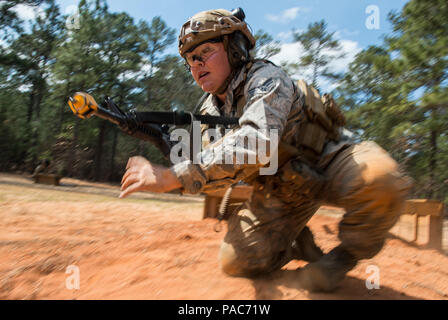 U.S. Air Force Senior Airman Megan Mallory, 1st Combat Camera combat broadcaster, learns how to fire an M4 carbine rifle while bounding forward during exercise Scorpion Lens, March 9, 2016 at Fort Jackson, S.C. Combat Camera airmen and soldiers practiced maneuvering and firing first without ammo, then blanks, and a final run with live ammo hitting popup targets. (U.S. Air Force photo by Staff Sgt. Perry Aston) - Stock Photo