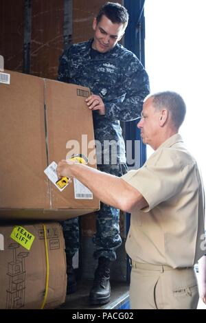 160315-N-XT613-015 SIGONELLA, Sicily (March 15, 2016) Rear Adm. James McNeal, commander of Naval Supply Systems Command (NAVSUP) Global Logistics Support, center, assists NAVSUP Fleet Logistics Center Sigonella personnel with sorting mail on board Naval Air Station Sigonella. McNeal is touring various commands in the U.S. 6th Fleet area of operation to improve his working knowledge of each command in order to better facilitate their supply requirements. (U.S. Navy photo by Shannon R. Haney/Released) - Stock Photo