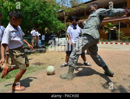Senior Airman Joseph Anderson, from the 67th Aircraft Maintenance Squadron, Kadena Air Base, Japan, plays soccer with students during the Exercise Cope Tiger 16 combined civic action engagement at Thong Chai Wittaya Primary School, Korat, Thailand, March 15, 2016. The combined civic action engagement provides an outlet for the countries participating in Cope Tiger to give back to the community surrounding Korat Royal Thai Air Force Base. Exercise Cope Tiger is multilateral field training exercise and includes more than 1,200 personnel from the United States, Thailand and Singapore. The purpose - Stock Photo