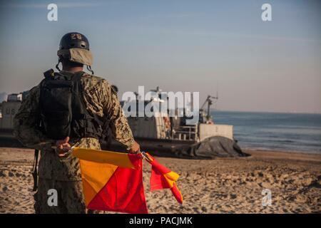 U.S. Navy sailor Seaman Joshua Hall, Naval Beach Party, Naval Beach Unit 7(NBU 7)  signals a Landing Craft Air Cushion assigned to NBU 7 during Exercise Ssang Yong 16, Dogu Beach, Pohang, South Korea, March 17, 2016.  Ssang Yong 16 is a biennial combined amphibious exercise conducted by U.S. forces with the Republic of Korea Navy and Marine Corps, Australian Army and Royal New Zealand Army forces in order to strengthen interoperability and working relationships across a wide range of military operations.  The Marines and sailors of the 31st MEU are currently deployed aboard the Bonhomme Richar - Stock Photo
