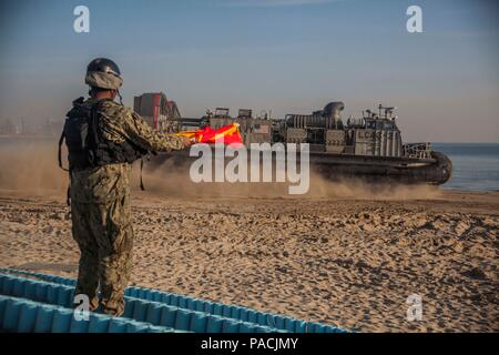 U.S. Navy sailor Seaman Joshua Hall, Naval Beach Party, Naval Beach Unit 7(NBU 7)  signals a Landing Craft Air Cushion assigned to NBU 7 during Exercise Ssang Yong 16, Dogu Beach, Pohang, South Korea, March 17, 2016. Ssang Yong 16 is a biennial combined amphibious exercise conducted by U.S. forces with the Republic of Korea Navy and Marine Corps, Australian Army and Royal New Zealand Army forces in order to strengthen interoperability and working relationships across a wide range of military operations. The Marines and sailors of the 31st MEU are currently deployed aboard the Bonhomme Richard  - Stock Photo