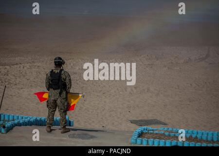 U.S. Navy sailor Seaman Joshua Hall, Naval Beach Party, Naval Beach Unit 7 (NBU 7) signals a Landing Craft Air Cushion assigned to NBU 7 carrying 31st Marine Expeditionary Unit personnel and equipment during Exercise Ssang Yong 16, Dogu Beach, Pohang, South Korea, March 17, 2016. Ssang Yong 16 is a biennial combined amphibious exercise conducted by U.S. forces with the Republic of Korea Navy and Marine Corps, Australian Army and Royal New Zealand Army forces in order to strengthen interoperability and working relationships across a wide range of military operations.  The Marines and sailors of - Stock Photo