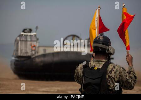 U.S. Navy sailor Seaman Joshua Hall, Naval Beach Party, Naval Beach Unit 7(NBU 7) signals a Landing Craft Air Cushion assigned to NBU 7 to pick up 31st Marine Expeditionary Unit personnel and equipment during Exercise Ssang Yong 16, Dogu Beach, Pohang, South Korea, March 17, 2016. Ssang Yong 16 is a biennial combined amphibious exercise conducted by U.S. forces with the Republic of Korea Navy and Marine Corps, Australian Army and Royal New Zealand Army forces in order to strengthen interoperability and working relationships across a wide range of military operations.  The Marines and sailors o - Stock Photo