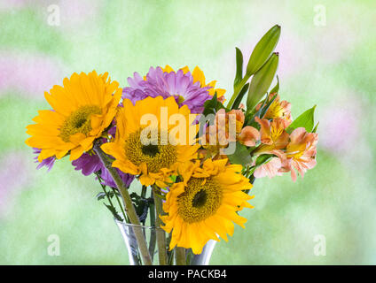 Attractive  bouquet arrangement of multi colored flowers in clear glass vase - Stock Photo