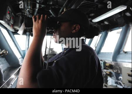 160321-N-VD165-125 HONG KONG (March 21, 2016) Ensign Pauline Langston uses binoculars to search for surface contacts on the bridge of amphibious assault ship USS Boxer (LHD 4). The Boxer Amphibious Ready Group, 13th Marine Expeditionary Unit team are visiting Hong Kong during their first port visit since departing San Diego on deployment Feb. 12. While in port the Sailors and Marines have the opportunity to enjoy local culture and cuisine, attend organized tours, and participate in cultural exchanges and sporting events with local groups. (U.S. Navy photo by Mass Communication Specialist 2nd C - Stock Photo