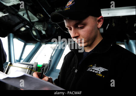 160321-N-VD165-124 HONG KONG (March 21, 2016) Quartermaster 3rd Class Ryan Burnette compares gyro repeaters on the bridge of amphibious assault ship USS Boxer (LHD 4). The Boxer Amphibious Ready Group, 13th Marine Expeditionary Unit team are visiting Hong Kong during their first port visit since departing San Diego on deployment Feb. 12. While in port the Sailors and Marines have the opportunity to enjoy local culture and cuisine, attend organized tours, and participate in cultural exchanges and sporting events with local groups. (U.S. Navy photo by Mass Communication Specialist 2nd Class Jose - Stock Photo