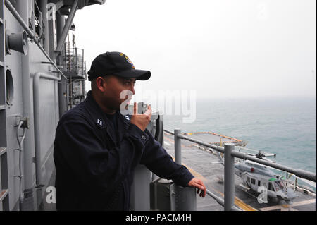160321-N-VD165-109 HONG KONG (March 21, 2016) Lt. Julius Dabu communicates with the sea and anchor detail as amphibious assault ship USS Boxer (LHD 4) prepares to arrive in Hong Kong. The Boxer Amphibious Ready Group, 13th Marine Expeditionary Unit team are visiting Hong Kong during their first port visit since departing San Diego on deployment Feb. 12. While in port the Sailors and Marines have the opportunity to enjoy local culture and cuisine, attend organized tours, and participate in cultural exchanges and sporting events with local groups. (U.S. Navy photo by Mass Communication Specialis - Stock Photo