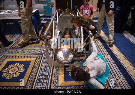 NATIONAL HARBOR, Md. (Apr. 2, 2017) Darby McCoy, 11, tries out a human-powered submarine as her sister, Jae, 8, and friend Aria Raphael, 9, and her sister Nora, 7, watch, during the 2017 Naval Stem Exposition, co-sponsored by the Navy League of the United States and the Office of Naval Research (ONR). The event offers hands-on activities and provides an introduction to naval STEM careers and educational opportunities including information about the 2017 International Submarine Races. - Stock Photo