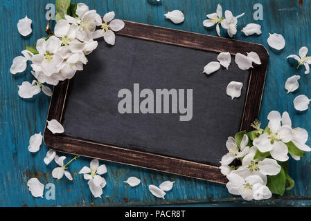 Vintage blank chalkboard or school slate is on an old blue rustic wooden background with white apple flowers, with space for text or message - Stock Photo
