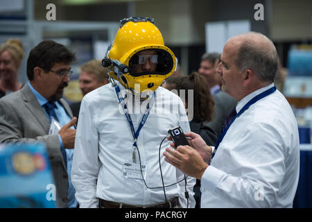 WASHINGTON (Jul. 20, 2017) Dennis Gallagher, an engineer from the Naval Surface Warfare Center, Panama City, explains the Divers Augmented Vision Display (DVAD) to an attendee during the Office of Naval Research's Naval Future Force Science and Technology (S&T) EXPO at the Walter E. Washington Convention Center. The DAVD is a high-resolution, see-through heads-up display (HUD) embedded directly inside of a diving helmet that enables divers to have real-time visual display of everything from sector sonar, text messages, diagrams, photographs and even augmented reality videos. - Stock Photo