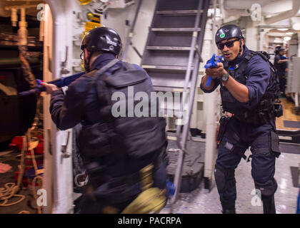 160321-N-GW139-069 PACIFIC OCEAN (March 21, 2016) Fire Controlman 1st Class Charles Spears, right, clears a passageway during a visit, board, search and seizure (VBSS) team practice aboard Arleigh Burke-class guided missile destroyer USS Fitzgerald (DDG 62). Fitzgerald is on patrol in the 7th Fleet area of operations in support of security and stability in the Indo-Asia-Pacific. (U.S. Navy photo by Mass Communication Specialist 3rd Class Eric Coffer/Released) - Stock Photo