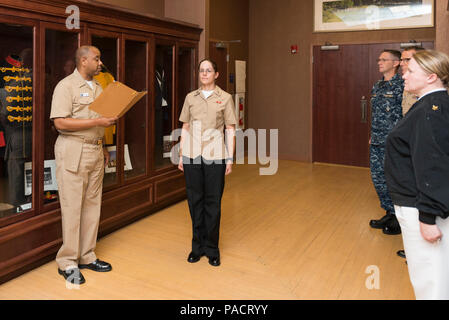WASHINGTON (Aug. 8, 2017) Musician 1st Class Sarah Demy (center) stands at attention during her pinning ceremony.  Sailors assigned to U.S. Navy Band are promoted to E6 upon completion of basic training. - Stock Photo