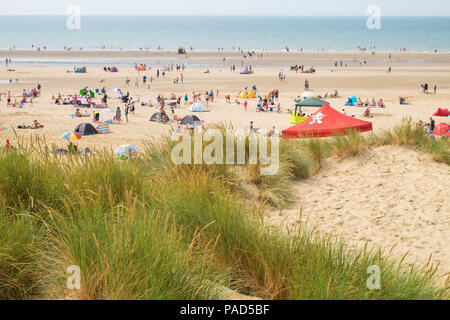 Camber Sands, East Sussex, UK. 22nd Jul, 2018. UK Weather: Hot and sunny weather in camber with scores of people hitting the beach early as this is predicted to be another scorcher of a day. Temperatures are expected to exceed 25°C. Sand dunes and sunbathers on a hot summers day. Photo Credit: Paul Lawrenson / Alamy Live News - Stock Photo