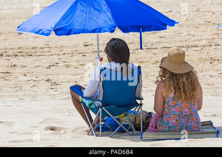 Bournemouth, Dorset, UK. 22nd July 2018. UK weather: hot and sunny at Bournemouth beaches, as sunseekers head to the seaside to soak up the sun. Couple sitting on beach under parasol. Credit: Carolyn Jenkins/Alamy Live News - Stock Photo