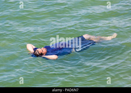 Bournemouth, Dorset, UK. 22nd July 2018. UK weather: hot and sunny at Bournemouth beaches, as sunseekers head to the seaside to soak up the sun. Male cooling down floating in the sea. Credit: Carolyn Jenkins/Alamy Live News - Stock Photo