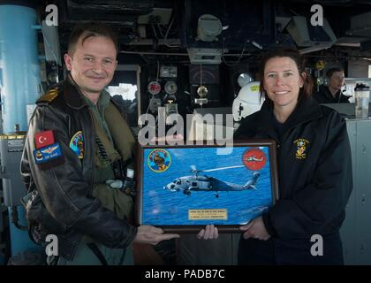 160328-N-FQ994-259 MEDITERRANEAN SEA (March 28, 2016) Cmdr. Andria Slough, USS Porter (DDG 78) commanding officer, right, accepts a gift from Turkish Navy Cmdr. Emin Keskin, 352 Helo Squadron, aboard the ship March 28, 2016. Porter, an Arleigh Burke-class guided-missile destroyer, forward-deployed to Rota, Spain, is conducting a routine patrol in the U.S. 6th Fleet area of operations in support of U.S. national security interests in Europe. (U.S. Navy Photo by Mass Communication Specialist 3rd Class Robert S. Price/Released) - Stock Photo