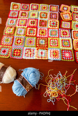 Brightly coloured granny square woollen baby blanket, traditional hand made crochet home handicraft, with balls of blue and white wool and threads - Stock Photo