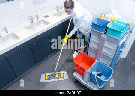 Cleaning lady mopping the floor in restroom - Stock Photo