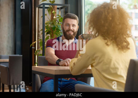 Smiling man with beard looking at curly girl wearing yellow blouse sitting in font of him in modern stylish restaurant. Having a date, feeling happy, satisfied. Green plant standing on background. - Stock Photo