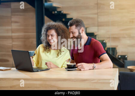 Laughing couple using laptop drinking coffee sitting in cafe. Students posing on wooden table standing in modern restaurant with wooden loft interior. Black metallic stairs on background. - Stock Photo