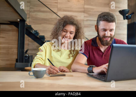 Studying students sitting in comfortable cafe, using laptop,smiling, laughing, drinking coffee, studying, writing notes. Posing on wooden table with black metallic stairs on background. - Stock Photo