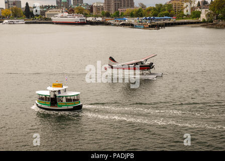 A small float plane taxiing past a small water taxi in calm waters of the harbour in Victoria on Vancouver Island - Stock Photo