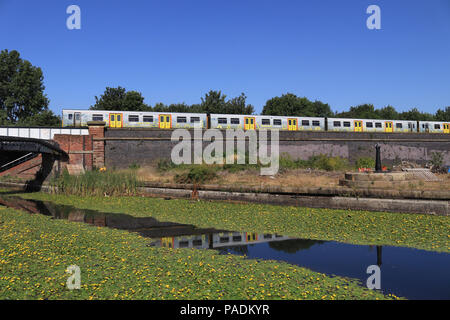 A Mersey rail train travelling from Liverpool to Southport crosses the Leeds and Liverpool canal near the Caroline Street footbridge in Bootle. - Stock Photo