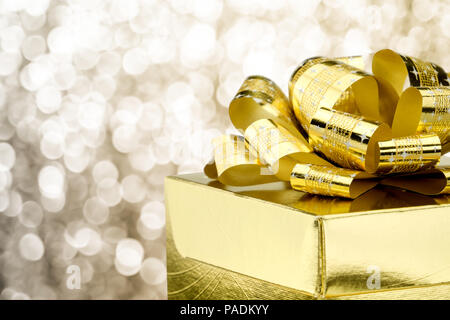 Close up Golden present box with big bow at bokeh white blur background, Leave space on top to adding your contentใ - Stock Photo