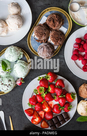 Selection of different ice cream scoops such as mint, chocolate and strawberry on marble background, top view - Stock Photo