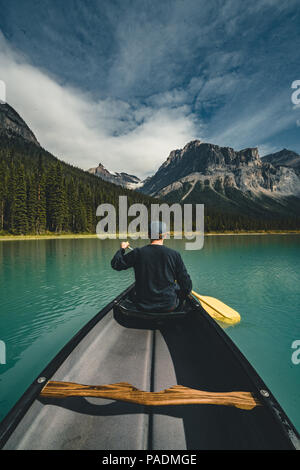 Young Man Canoeing on Emerald Lake in the rocky mountains canada with canoe and mountains in the background blue water. - Stock Photo