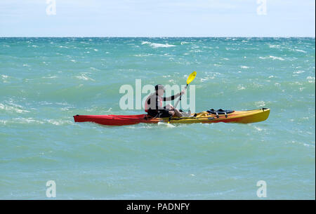 Man wearing life jacket paddling his Kayak in choppy seas off the coast of East Preston, West Sussex, UK. Direction East to West. - Stock Photo