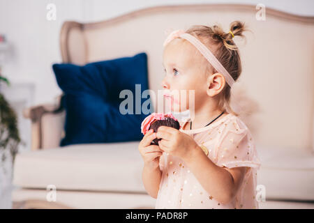 children's birthday. funny two-year-old Caucasian girl in pink dress standing to bedroom of house the background of couch and eating, holding cake des - Stock Photo