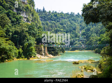 Beautiful scene of forest, river and suspension bridge in China Guizhou Huangguoshu scenery park. - Stock Photo