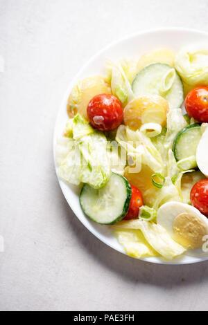 New potato, cherry tomatoes, lettuce, cucumber and egg mayo salad - Stock Photo