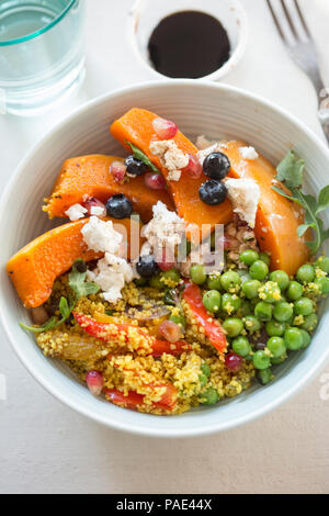 Couscous, red peppers, peas with butternut squash, blueberries and goat's cheese salad - Stock Photo