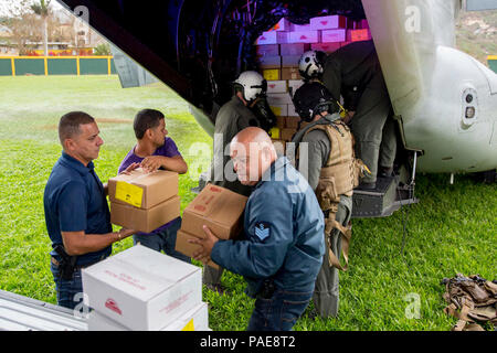 JAYUYA, Puerto Rico (Sept. 27, 2017) Marines assigned to Marine Medium Tiltrotor Squadron 162, embarked aboard the amphibious assault ship USS Kearsarge (LHD 3), and local volunteers unload food from an MV-22 Osprey in Jayuya, Puerto Rico. Kearsarge is assisting with relief efforts in the aftermath of Hurricane Maria. The Department of Defense is supporting the Federal Emergency Management Agency, the lead federal agency, in helping those affected by Hurricane Maria to minimize suffering and is one component of the overall whole-of-government response effort. - Stock Photo