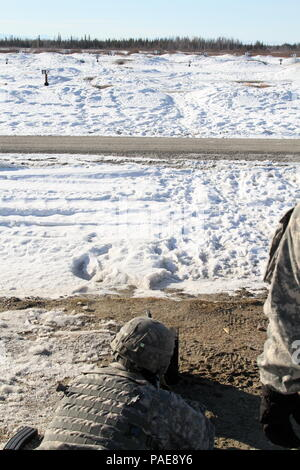 Pfc. Francisco Rodriguez, a M240B machine gunner with B Co., 1st Battalion, 24th Infantry Regiment, engages targets at a M4 range at Fort Wainwright, Alaska on March 24, 2016. Soldiers with 1-24 IN have to qualify expert with the M4 before they try out for the Expert Infantry Badge qualification that slated for the beginning of May. - Stock Photo