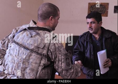Maj. Sourd Sakirn Hussen, training officer, Altun Kupri Iraqi Police Station, shakes hands with U.S. Army Staff Sgt. Robert Wade, squad leader, 1st Squad, 2nd Platoon, 218th Military Police Company, 317th Military Police Battalion, 49th Military Police Brigade, 3rd Infantry Division, after discussing plans for an upcoming training event for Iraqi policemen in Altun Kupri, Iraq, Jan. 3. The Soldiers visited the police station to talk discuss current events and training issues for the Iraqi police. - Stock Photo