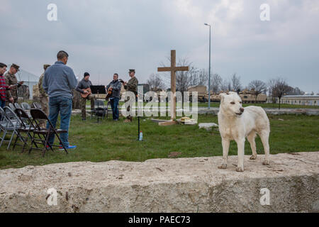 U.S. Service members give praise in song as a stray dog howls in unison during an Easter sunrise worship service aboard Mihail Kognalniceanu Air Base, Romania, March 27, 2016. Christians around the world celebrated Easter and the resurrection of Jesus Christ. (U.S. Marine Corps photo by Cpl. Kelly L. Street, 2D MARDIV COMCAM/Released) - Stock Photo