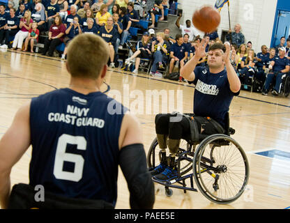 Hospital Corpsman 2nd Class Max Rohn passes to Explosive Ordnance Disposal Technician 1st Class John Kremer during the wheelchair basketball competition between special operations and the Navy/Coast Guard at the 2012 Warrior Games. More than 200 wounded, ill or injured service members from the U.S. and British armed forces are scheduled to compete in the Paralympics-style competition, May 1-5. - Stock Photo