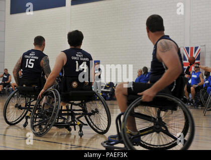 Team Navy/Coast Guard member retired Gunner's Mate Chief Hector Varela of San Diego and teammates, retired Hospital Corpsman 2nd Class Sonny Lemerande of Twentynine Palms, Calif., and retired Explosive Ordnance Disposal Technician 1st Class John Kremer of Buford, Ga., prepare to block a pass by an opposing team in a game of wheelchair basketball against Team Air Force during the 2013 Warrior Games May 14. The Warrior Games includes competitions in archery, cycling, seated volleyball, shooting, swimming, track and field, and wheelchair basketball. The goal of the Warrior Games is not necessaril - Stock Photo