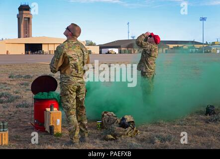 Members of the 26th Special Tactics Squadron watch as teammates parachute down from an aircraft overhead March 25, 2016, at Cannon Air Force Base, N.M. Dozens of 26th STS members performed routine practice jumps over the Cannon flightline, and relied on ground crews to use signals to help them safely touch-down at the designated landing zone. (U.S. Air Force photo/Staff Sgt. Alexx Pons) - Stock Photo